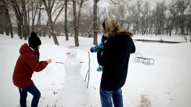 家族で雪だるまを作る - 30代点の映像素材/bロール
