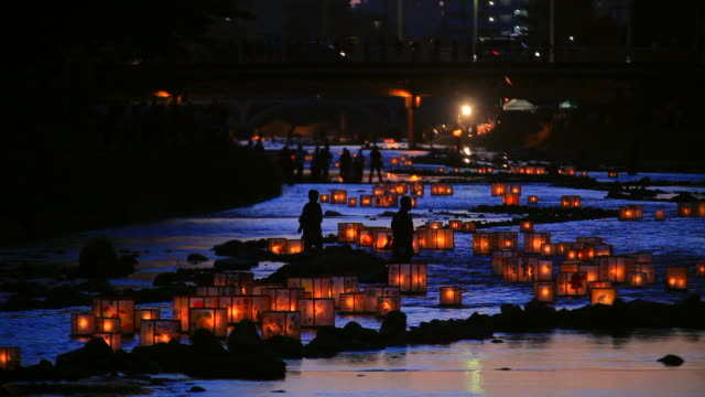 making a wish with the lanterns on the flowing river in kanazawa, japan - 伝統的な祭り点の映像素材/bロール