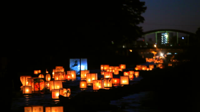 making a wish with the lanterns on the flowing river in kanazawa, japan - ランプ点の映像素材/bロール