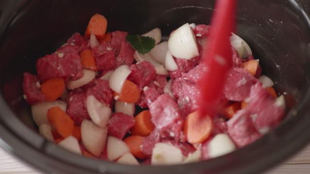 vídeos de stock e filmes b-roll de making beef stew in slow cooker - strogonoff