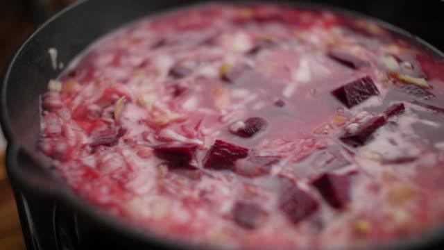 家庭の台所でビートルートリゾットを作る - 調理用へら類点の映像素材/bロール