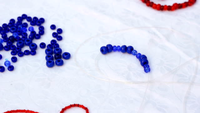 hd: making blue bracelet for decoration - bracelet stock videos and b-roll footage