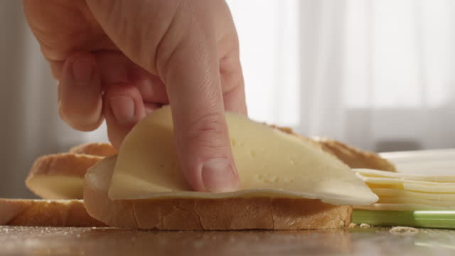 making bread with cheese sandwich at the table in the kitchen - サンドイッチ作り点の映像素材/bロール