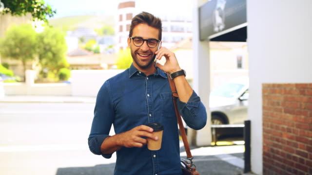 vidéos et rushes de faire des appels pendant sa course de café du matin - trentenaire