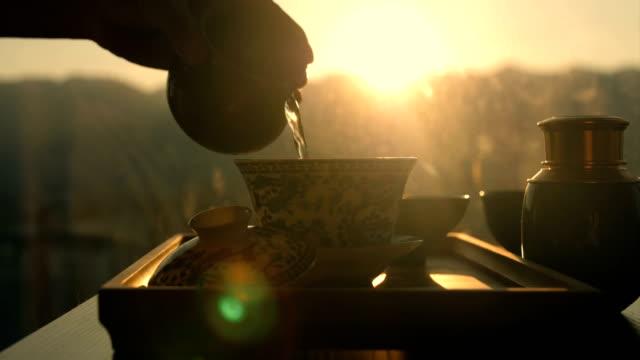 vídeos de stock e filmes b-roll de making china tea,pouring water into tea cup - chá bebida quente