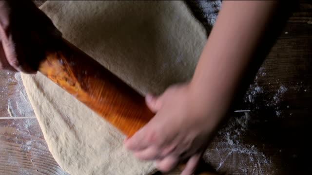 vídeos de stock, filmes e b-roll de fazer massa por mãos femininas no fundo da mesa de madeira - rolo de pastel
