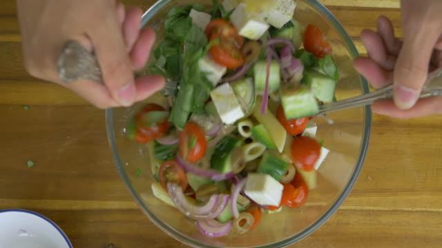 vídeos y material grabado en eventos de stock de haciendo ensalada de pasta al estilo griego - table top view