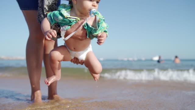 vídeos de stock e filmes b-roll de making his first steps on the beach - fralda