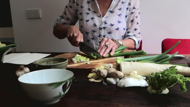 Making kimchi: chopping scallions