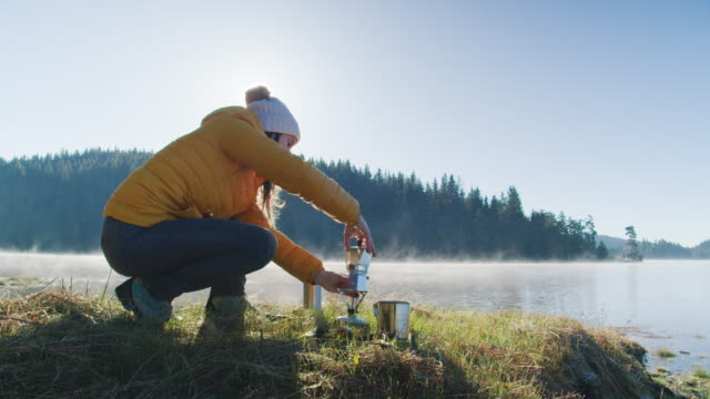 making morning coffee in the nature. hot drink in a cold weather while camping outdoors. getting away from it all. end of the covid-19 outbreak. - coffee drink stock videos & royalty-free footage