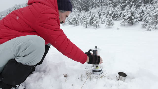 making morning coffee in the nature. hot drink in a cold weather while camping outdoors in the white winter mountains. getting away from it all during covid-19 pandemic. - northern europe stock videos & royalty-free footage