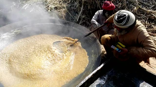 making of brown sugar or jaggery (sugarcane molasses is being boiling to evaporate the water from it) - only mature men stock videos & royalty-free footage