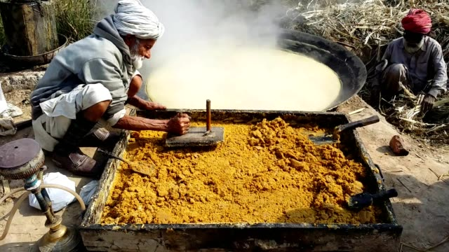 vidéos et rushes de making of brown sugar or jaggery (breaking and pressing hard sugarcane molasses to make brown sugar) - seulement des hommes d'âge mûr