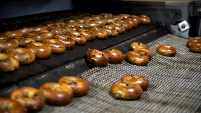 Making-of die frischen heißen leckeren Bagels in der Bäckerei Fabrik: Bagels herauskommt aus dem Ofen