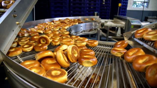 stockvideo's en b-roll-footage met maken van de verse hete lekkere bagels in de backery van de fabriek - bagels vervoert voor het sorteren op de transportband. - bakkerij