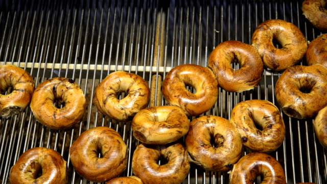 making of the fresh hot tasty bagels at the backery's factory - bagels are transporting for sorting on the conveyor. - group of objects stock videos & royalty-free footage