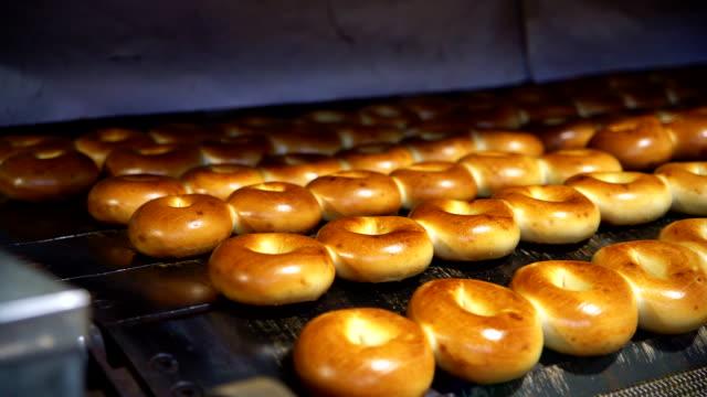 Maken van de verse hete lekkere bagels in van de backery fabriek: vliegtuig bagels komt uit de oven. 4K UHD video met panoramische beweging.