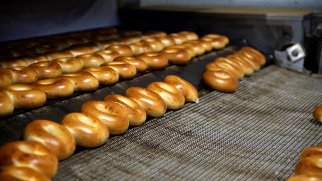 Making-of die frischen heißen leckeren Bagels in der Bäckerei Fabrik: Flugzeug Bagels herauskommt aus dem Ofen