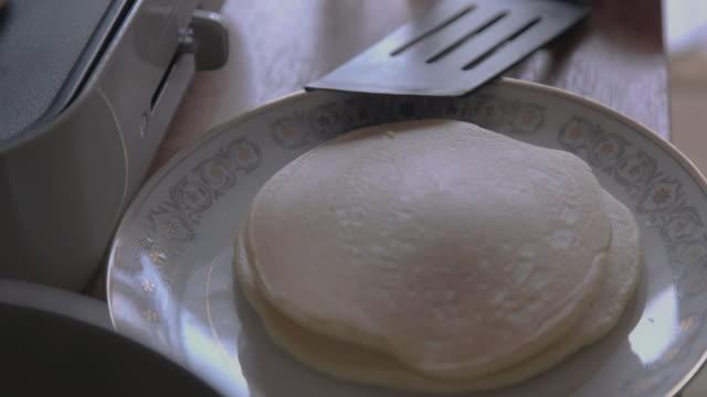 vídeos de stock, filmes e b-roll de making pancake on hotplate. - espátula