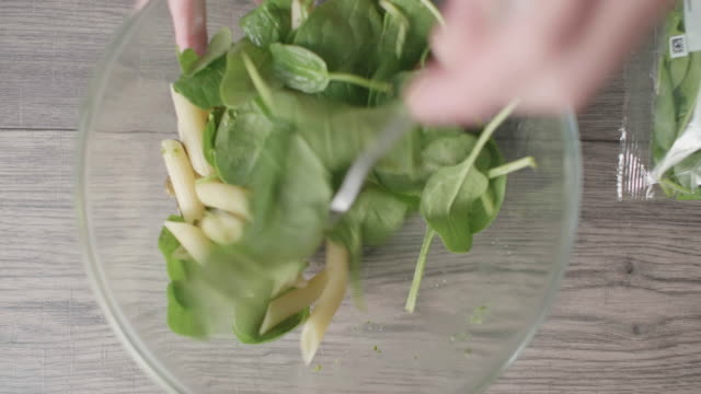 making penne pasta salad with green pesto sauce - spinach salad stock videos & royalty-free footage