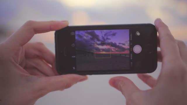 vidéos et rushes de faire la photo du coucher du soleil sur la plage - filmer