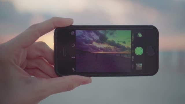 Making photo of sunset on beach