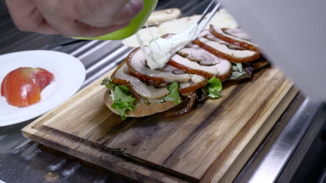 making pork fillet sandwich with lettuce and cream - sandwich stock videos & royalty-free footage