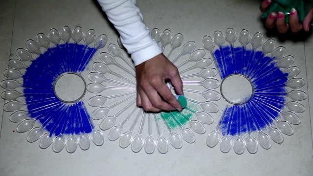 Making Rangoli by using plastic spoon on Diwali festival
