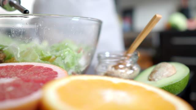 vidéos et rushes de salade de fabrication avec le pamplemousse et l'avocat - salade verte
