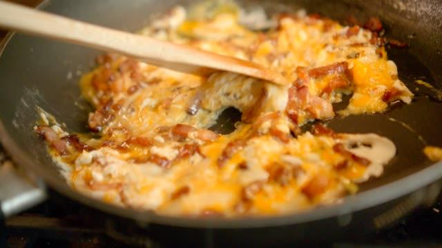 vídeos de stock, filmes e b-roll de fazendo ovos mexidos com bacon para o pequeno almoço - ovo mexido