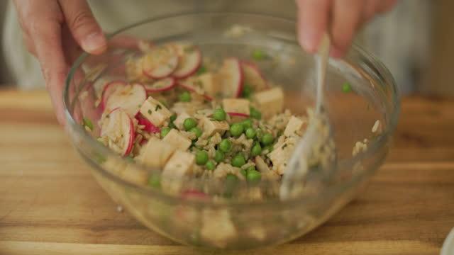ビーガン豆腐、エンドウ豆、玄米サラダを作る - 玄米点の映像素材/bロール