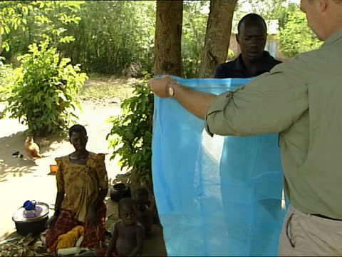 new 'malaria net' trial; uganda: namasagali: seq lydia shows snow the new mosquito net hanging inside her hut, snow asks her if atim has had malaria... - female doctor stock videos & royalty-free footage