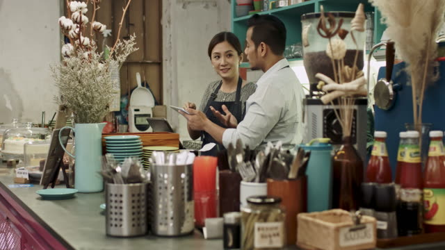 Malay business couple owner checking digital tablet at bar counter