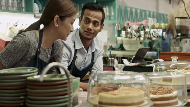 Malay business couple owner talking at coffee shop counter