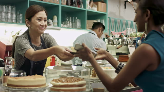 Malay Chinese woman serving cake at coffee shop