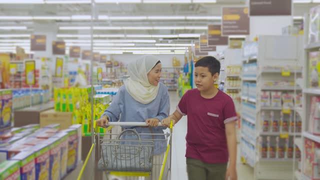 stockvideo's en b-roll-footage met maleise moeder met hijab en zoon duwen winkelwagentje winkelen in supermarkt tijdens weekend - dairy product