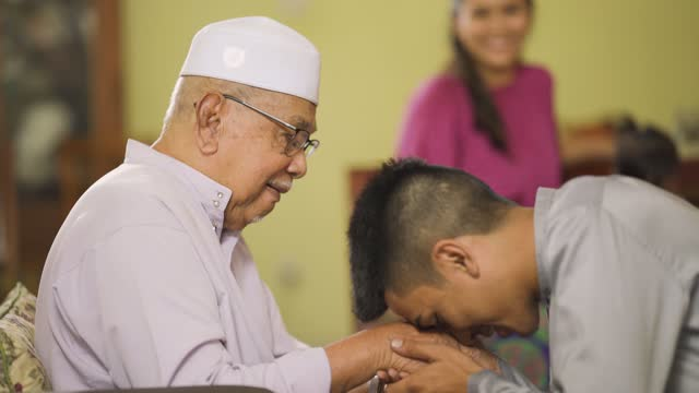 malay muslim grandson in traditional clothing showing apologize gesture to his grandfather during aidilfitri celebration malay family at home celebrating hari raya - traditional ceremony stock videos & royalty-free footage