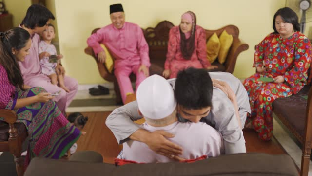 malay muslim grandson in traditional clothing showing apologize gesture to his grandfather during aidilfitri celebration  malay family at home celebrating hari raya - malaysian culture stock videos & royalty-free footage