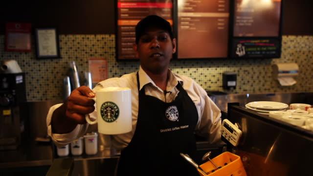 vídeos de stock, filmes e b-roll de malay starbucks barista serves beverage - starbucks