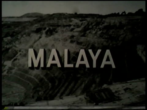 malaya' superimposed over strip mine. vs southeast asian tin mine workers in conical straw hats standing in elevated water trough, using hoe, pushing... - tin mine stock videos & royalty-free footage