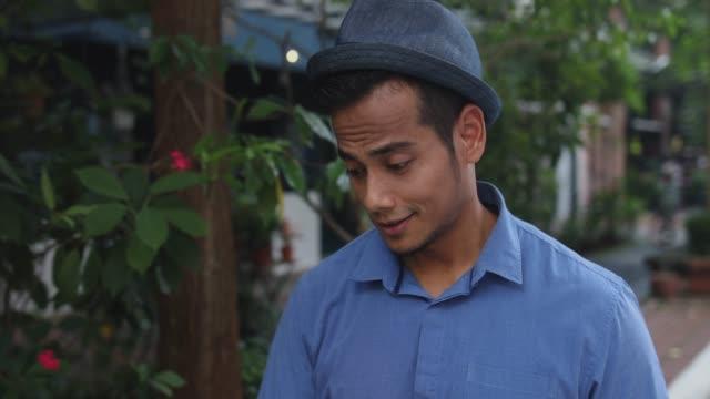 Malaiische Mann zu Fuß und lächelnd auf der Straße
