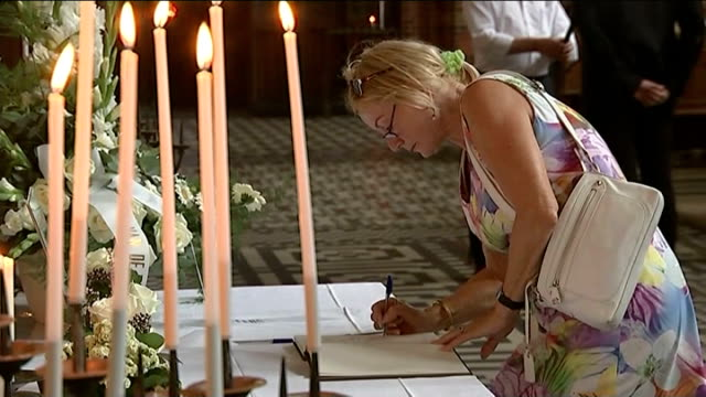 Dutch victims NETHERLANDS Hilvursum INT Priest hugging grieving woman in church Close Shot Candles beside memorial document with number '298' Woman...