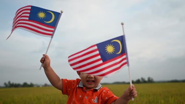 vídeos y material grabado en eventos de stock de día de la independencia de malasia un niño chino asiático ondeando con la bandera de malasia en el campo padi disfrutando de la luz del sol de la mañana y se siente orgulloso y feliz - malaysian culture