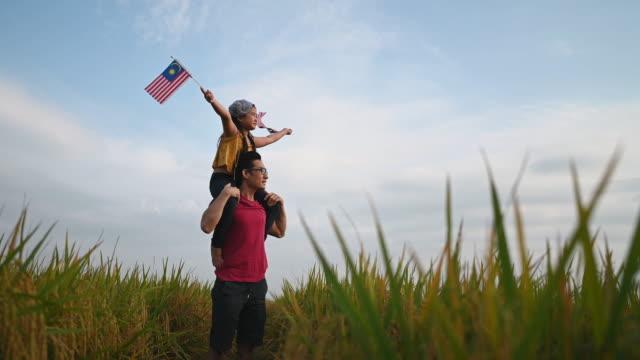 vídeos y material grabado en eventos de stock de día de la independencia de malasia una joven china asiática sosteniendo la bandera de malasia en el campo padi llevado por su padre en su hombro padre disfrutando de la luz del sol de la mañana y se siente orgulloso y feliz - malaysian culture