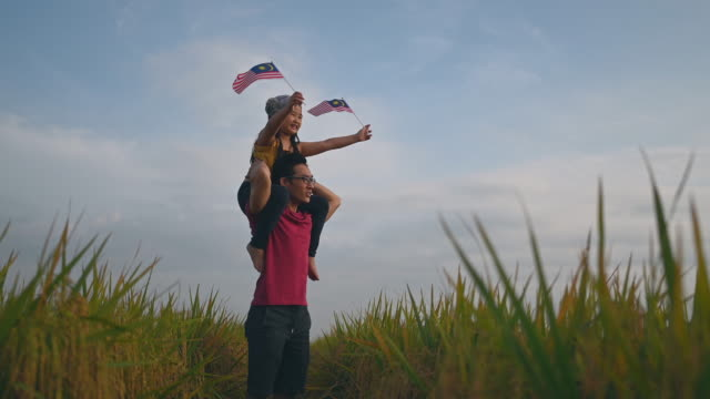 malaysia independence day an asian chinese young girl holding malaysia flag at padi field carried by her father on her father shoulder enjoying morning sunlight and feel proud and happy - cultura malesiana video stock e b–roll
