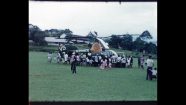 Malaysian children gathered around soldiers in field with a US Marine Kaman HH43 helicopter nearby From the home movie collection of Jack Dennis...