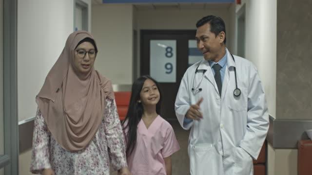 vídeos de stock, filmes e b-roll de médico da malásia andando no corredor do hospital com a criança doente e a mãe dela - vestuário modesto