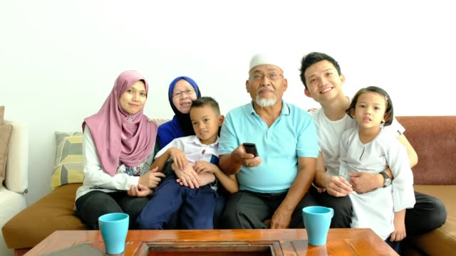 malaysian family on the couch watching tv - cultura malesiana video stock e b–roll