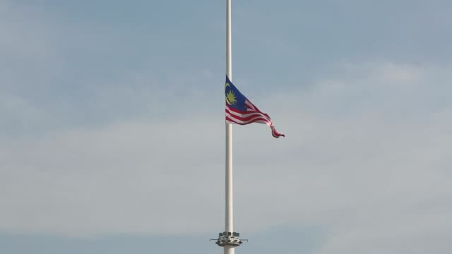 a malaysian flag hangs at halfmast at merdeka square in kuala lumpur malaysia on sunday july 20 a malaysian flag right flies at half mast in kuala... - merdeka square kuala lumpur stock videos & royalty-free footage