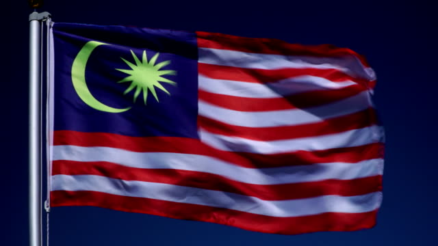 4K: Malaysian Flag on Flagpole in front of Blue Sky outdoors (Malaysia)